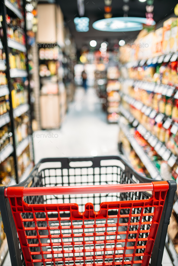 Shopping cart between shelves in food store - Stock Photo - Images