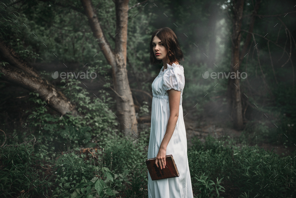 Female victim in white dress holds book in hand - Stock Photo - Images
