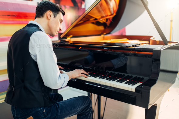 Male pianist at the classical black grand piano - Stock Photo - Images
