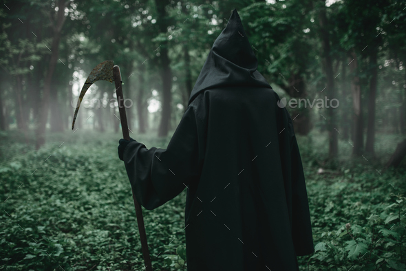Death with a scythe in the dark misty forest - Stock Photo - Images
