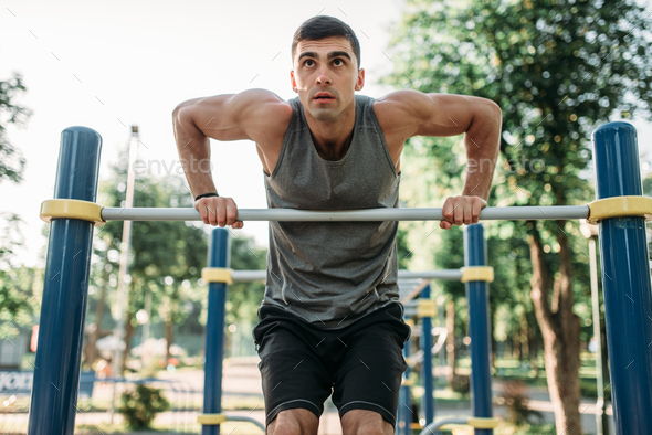 Man doing exercise on horizontal bar outdoor - Stock Photo - Images
