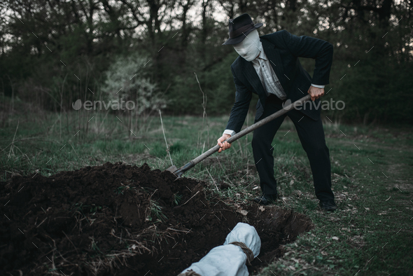 Bloody murderer is digging a grave for the victim - Stock Photo - Images
