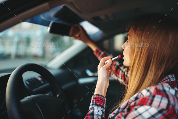 Woman driver paints her lips with lipstick in car - Stock Photo - Images