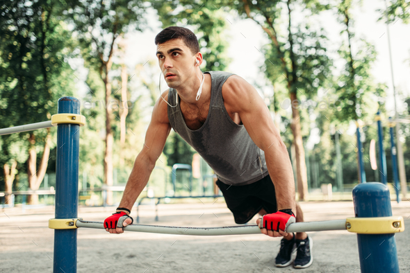 Man doing push-up exercise using horizontal bar - Stock Photo - Images