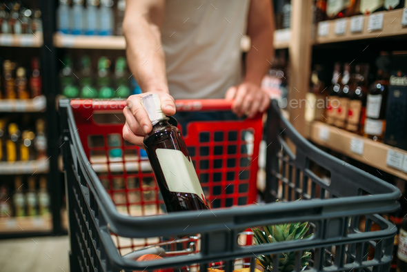 Male person put bottle of wine in a cart - Stock Photo - Images