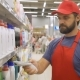 Supermarket Employee in Red Uniform Scanning Cleaners Barcode in Modern Retail Store - VideoHive Item for Sale