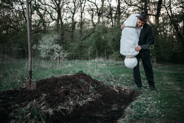 Murderer throws victim's body into the grave - Stock Photo - Images