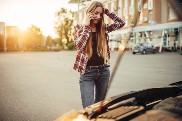 Car breakdown, sad woman against open bonnet - Stock Photo - Images