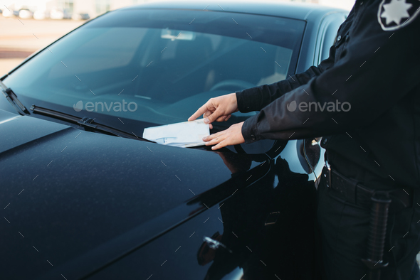 Male policeman in uniform writes a fine on road - Stock Photo - Images