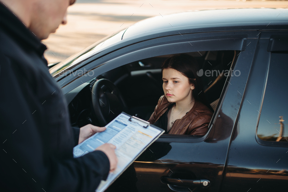 Policeman in uniform writes fine to female driver - Stock Photo - Images