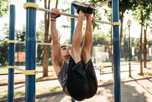 Man doing stretching exercise using horizontal bar - Stock Photo - Images