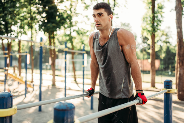 Male athlete exercises on parallel bars outdoor - Stock Photo - Images