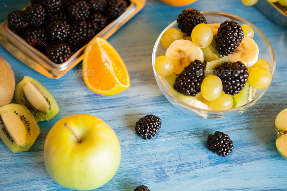 Diet fresh tasty mix of fruits in a bowl on a wooden table - Stock Photo - Images