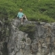 Young Hipster Woman Is Sitting on the Edge on the Grass of Tall Wall of Rock - VideoHive Item for Sale