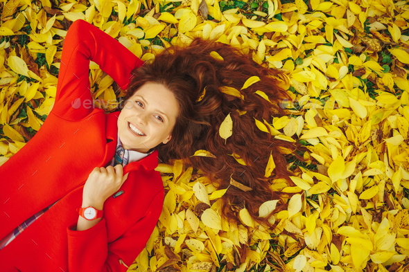 Smiling womn autumn leaves in hair - Stock Photo - Images