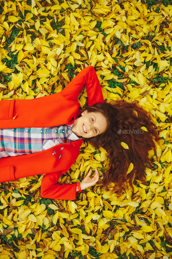 Young beautiful lady surrounded autumn leaves - Stock Photo - Images