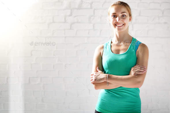 Portrait of happy smiling caucasian young sports woman against w - Stock Photo - Images