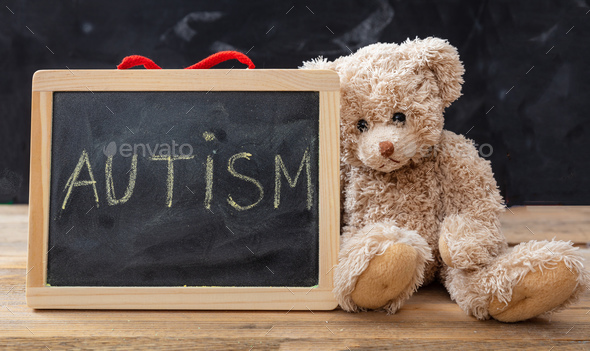 Teddy bear and a blackboard. Autism text drawing on the blackboard - Stock Photo - Images