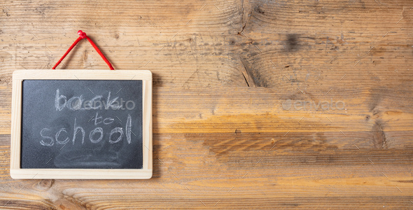 Back to school on blackboard with frame hanging on wooden wall, banner, copy space - Stock Photo - Images