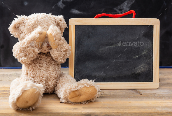 Teddy bear covering eyes and a blank blackboard, space for text - Stock Photo - Images