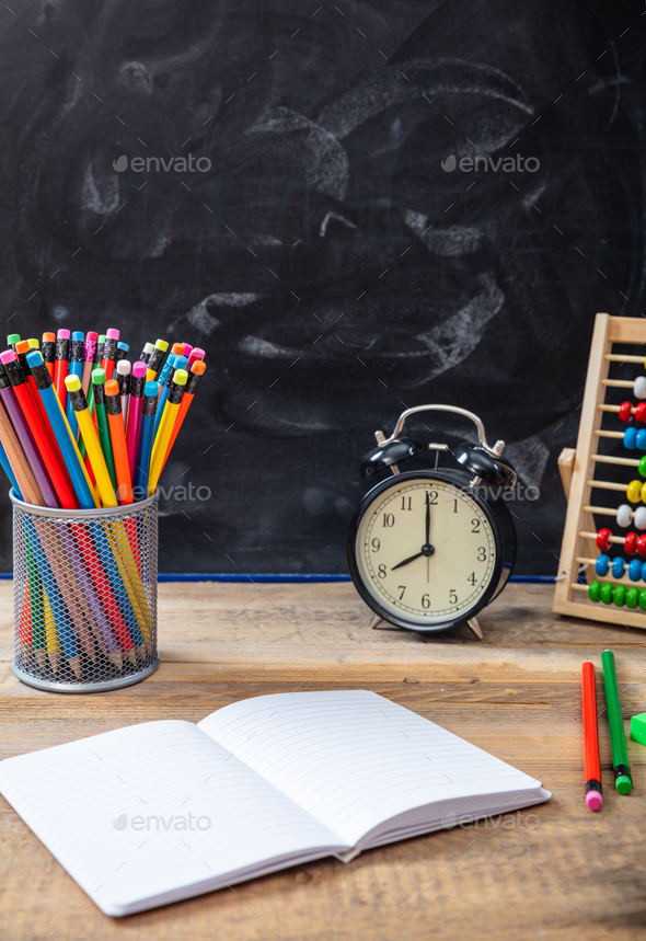 School supplies and alarm clock on wooden desk, blackboard background - Stock Photo - Images