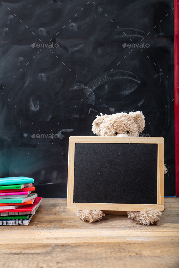 Back to school. Teddy bear and blank blackboard with frame on wooden desk - Stock Photo - Images