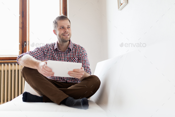 Handsome man sitting on sofa using a digital tablet - Stock Photo - Images