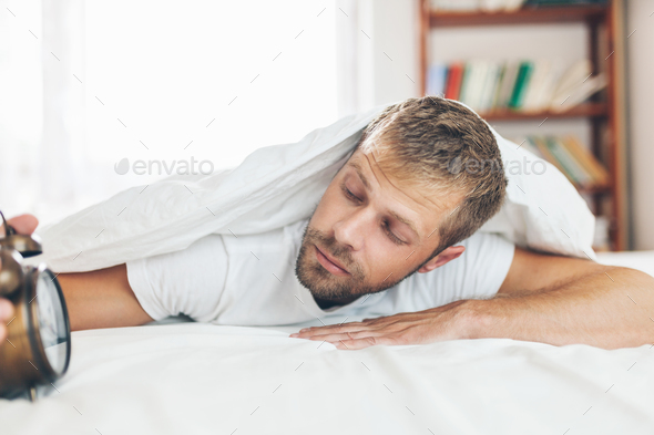 Man finding it difficult to wake up in the morning - Stock Photo - Images
