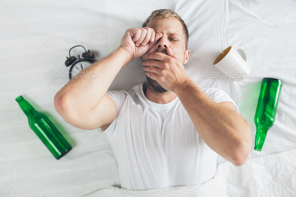 Young man in bed the morning after night out drinking - Stock Photo - Images