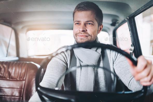 Handsome man sitting inside his vintage car - Stock Photo - Images