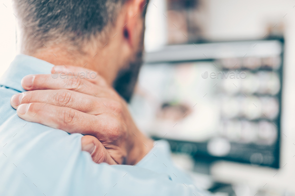 Office worker with neck pain from sitting at desk all day - Stock Photo - Images