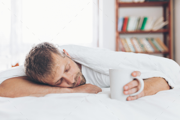 Man trying to wake up in the morning - Stock Photo - Images