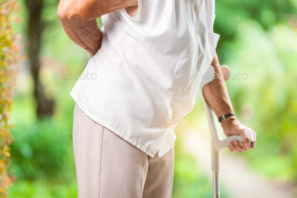 Elderly woman outdoors with back pain - Stock Photo - Images