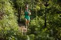 Female trail runner running in sunny forest - PhotoDune Item for Sale