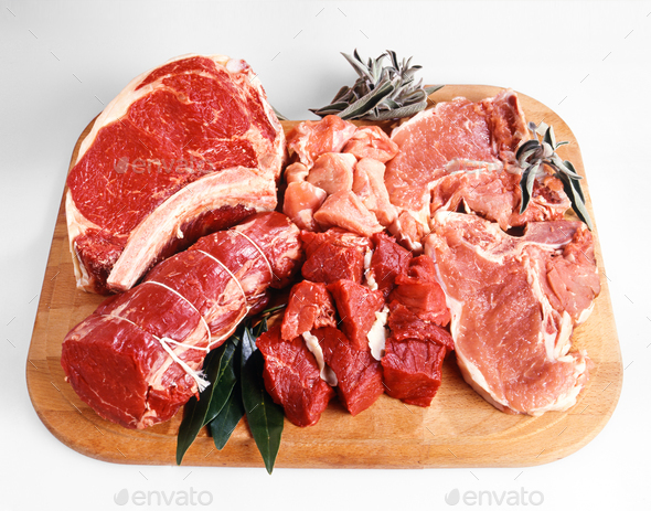 Red meats displayed on wooden cutting board - Stock Photo - Images