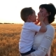 A Happy Mother Holds a Child in Her Arms in a Field of Wheat Against a Sunset Background - VideoHive Item for Sale