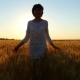 Young Attractive Girl Is Walking Along a Wheat Field in a White Dress on a Sunset Background - VideoHive Item for Sale