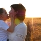 A Happy Mother Holds a Child in Her Arms in a Field of Wheat Against a Sunset Background. The Child - VideoHive Item for Sale