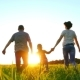 Happy Young Family with a Child Running on the Green Lawn - VideoHive Item for Sale