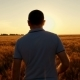 A Young Successful Farmer Walks the Field of Wheat Against the Backdrop of a Sunset - VideoHive Item for Sale
