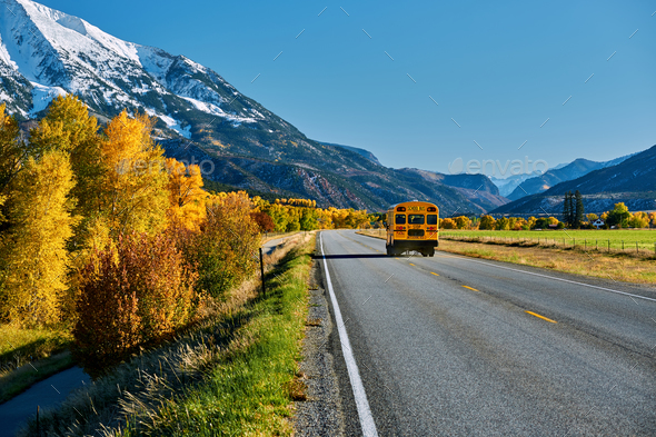School bus on highway in Colorado at autumn - Stock Photo - Images