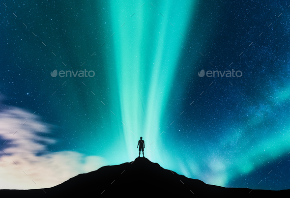 Northen lights and silhouette of standing man on the mountain - Stock Photo - Images