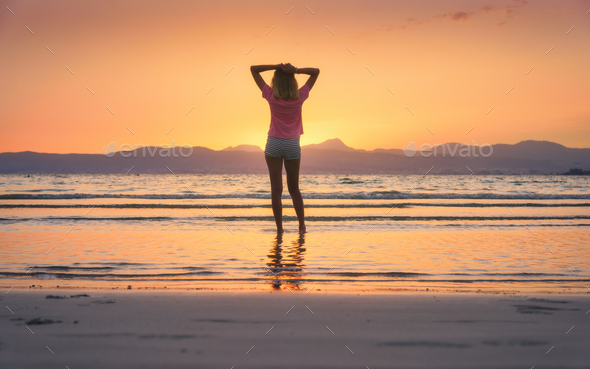 Young woman standing in sea with waves at sunset - Stock Photo - Images