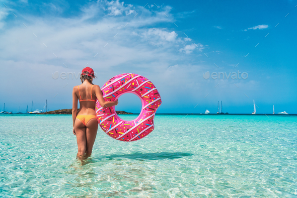 Young woman in bikini with pink donut swim ring in the sea - Stock Photo - Images