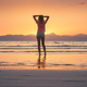 Young woman standing in sea with waves at sunset - PhotoDune Item for Sale