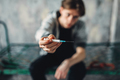 Male junkie reaching out hand with syringe - PhotoDune Item for Sale