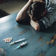 Male junkie at the table with drugs and syringe - PhotoDune Item for Sale