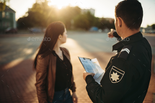 Police officer shows parking place to driver - Stock Photo - Images