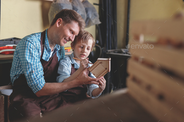 Father and son with a wooden house - Stock Photo - Images