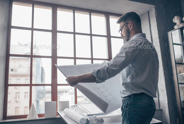 Mature architect with a project indoors - Stock Photo - Images